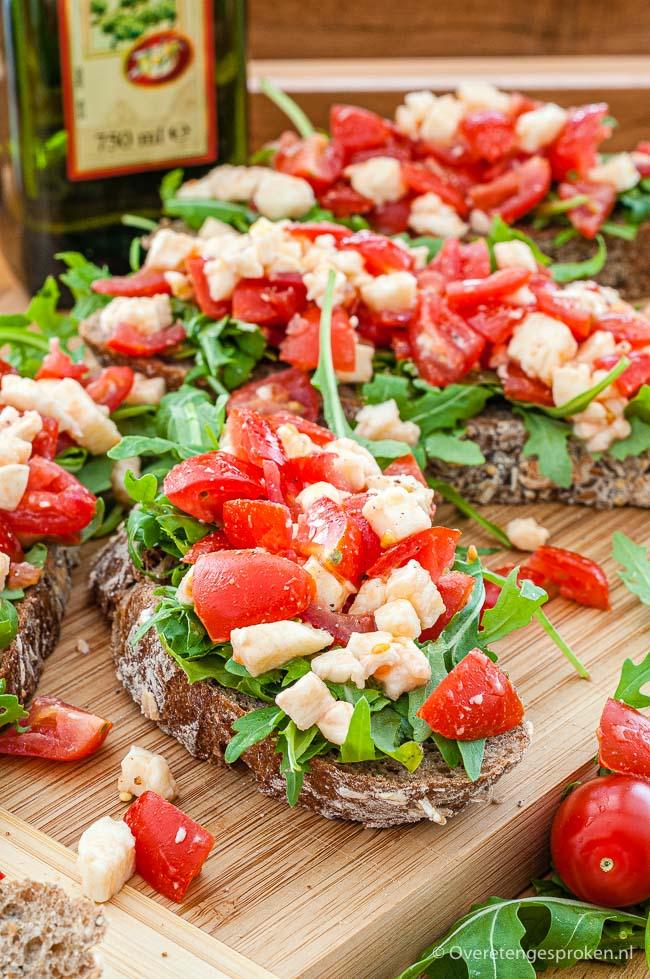 Bruschetta met mozzarella en tomaat - Fijngesneden mozzarella en tomaat samen met wat rucola op (getoast) brood. Te lekker om vanaf te blijven.