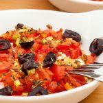 Feta met tomaat uit de oven - Grieks voorgerecht van warme feta bedekt met stukjes tomaat, zwarte olijven, lente-ui en oregano. Lekker met vers brood.