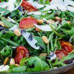 Salade van rucola, tomaatjes, pijnboompitjes, balsamicostroop en Parmezaanse kaas - Kleurrijke en smaakvolle salade. Door de tomaatjes op lage temperatuur in de oven te drogen krijgen ze extra smaak.
