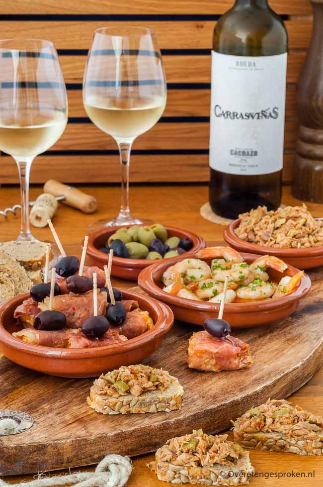 Spaanse borrelplank - Borrel in Spaanse sferen met een fijne plank vol kabeljauw met serranoham en arrabiata saus, tonijnsalade en knoflookgarnalen.