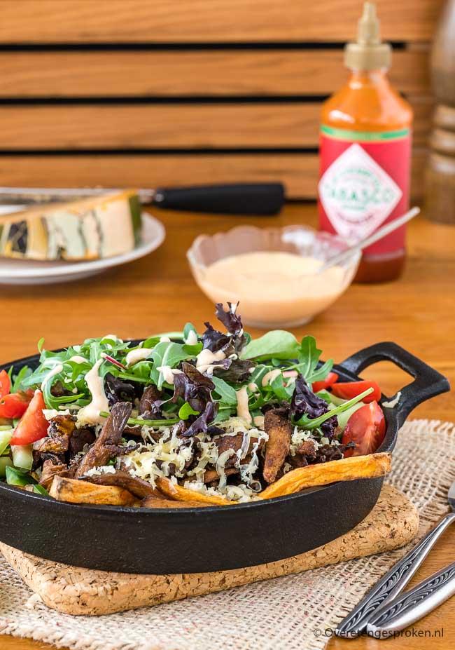 Vegetarische kapsalon - Zoete aardappelfrietjes, oesterzwamshoarma, frisse salade en afgetopt met een heelijke srirachasaus. Deze kapsalon wil je proeven!