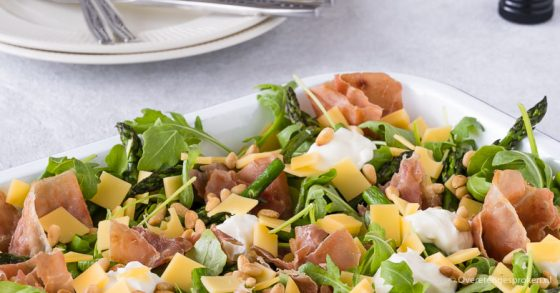 Salade met gegrilde groene asperges, serranoham, kaas en ricotta